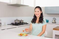Портрет молодой женщины есть салат в кухне Стоковое фото RF