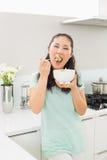 Портрет молодой женщины есть салат в кухне Стоковые Фотографии RF