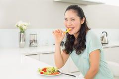 Портрет молодой женщины есть салат в кухне Стоковое Изображение RF