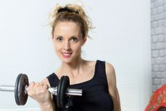 Портрет молодой женщины делая тренировку с гантелями, a фитнеса Стоковое Изображение RF