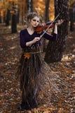 Портрет молодой женщины играя парк скрипки осенью Стоковое Изображение RF