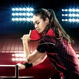 Портрет молодой женщины играя теннис на черноте стоковое фото