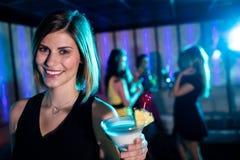 Портрет молодой женщины имея коктеиль Стоковые Изображения