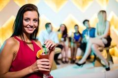 Портрет молодой женщины имея коктеиль Стоковая Фотография RF