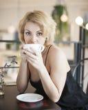 Портрет молодой женщины имея кофе на таблице ресторана Стоковые Фото