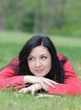 Портрет молодой женщины имея остатки с книгой на траве в Стоковое Изображение