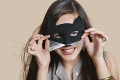 Портрет молодой женщины имитируя как кот пока смотрящ через маску глаза над покрашенной предпосылкой Стоковые Фото