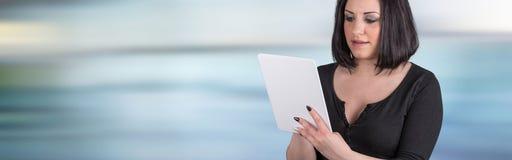 Портрет молодой женщины используя цифровую таблетку Стоковые Изображения RF