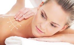 Портрет молодой женщины кладя на заднюю процедуру по массажа Стоковое Изображение