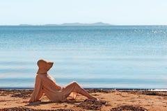 Портрет молодой женщины на пляже около wearin моря сидя Стоковое Изображение RF