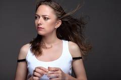 Портрет молодой женщины на серой предпосылке в белом танке t Стоковое фото RF