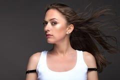 Портрет молодой женщины на серой предпосылке в белом танке t Стоковые Фотографии RF