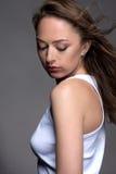 Портрет молодой женщины на серой предпосылке в белом танке t Стоковое Изображение RF