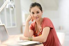 Портрет молодой женщины дома работая на компьтер-книжке Стоковое Изображение RF