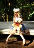 Портрет молодой женщины одетый как кукла сидя на стенде Стоковые Изображения RF