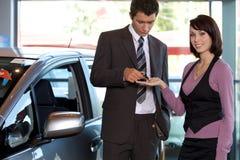 Портрет молодой женщины получая ключ автомобиля от продавца автомобилей Стоковые Фотографии RF