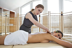 Портрет молодой женщины получая массаж от masseuse Стоковая Фотография RF