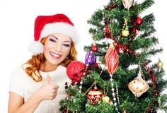 Портрет молодой женщины представляя около рождественской елки Стоковые Фото