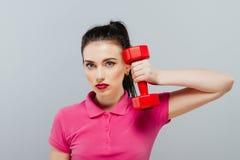 Портрет молодой женщины представляя с гантелями в спортзале Жизнь спорта Стоковые Изображения