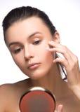 Портрет молодой женщины прикладывая сливк на ее милой стороне - белую предпосылку увлажнителя Способ и красотка Стоковое фото RF