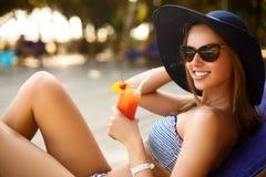 Портрет молодой женщины при стекло коктеиля охлаждая в тропическом солнце около бассейна на шезлонге с ладонью Стоковые Изображения