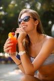 Портрет молодой женщины при стекло коктеиля охлаждая в тропическом солнце около бассейна на шезлонге с ладонью Стоковая Фотография