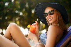 Портрет молодой женщины при стекло коктеиля охлаждая в тропическом солнце около бассейна на шезлонге с ладонью Стоковые Изображения RF