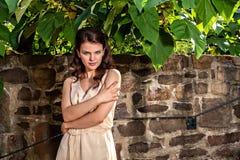 Портрет молодой женщины против старой каменной стены Стоковое Фото