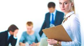 Портрет молодой женщины работая на офисе стоя с папкой Стоковые Фото