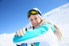 Портрет молодой женщины сидя в снеге Стоковые Изображения RF