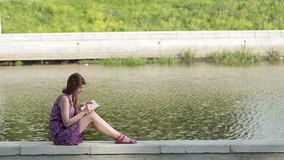 Портрет молодой женщины, сидя в сочинительстве парка в ее дневнике На банках реки акции видеоматериалы
