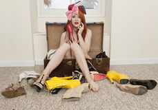 Портрет молодой женщины сидя в чемодане при обувь лежа на поле Стоковое Фото