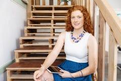 Портрет молодой женщины сидя на лестницах в офисе Стоковые Фотографии RF