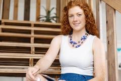 Портрет молодой женщины сидя на лестницах в офисе Стоковая Фотография
