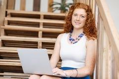 Портрет молодой женщины сидя на лестницах в офисе Стоковое Изображение