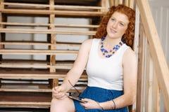 Портрет молодой женщины сидя на лестницах в офисе Стоковое фото RF
