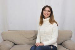 Портрет молодой женщины сидя на кресле Стоковые Изображения