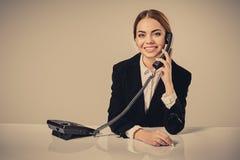 Портрет молодой женщины сидя на таблице и работе Стоковая Фотография