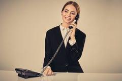 Портрет молодой женщины сидя на таблице и работе Стоковые Изображения