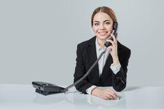 Портрет молодой женщины сидя на таблице и работе Стоковые Фото
