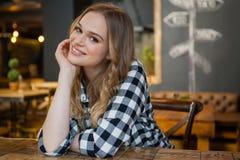 Портрет молодой женщины сидя на таблице Стоковая Фотография