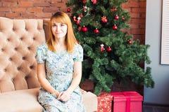 Портрет молодой женщины сидя около рождественской елки Стоковые Изображения