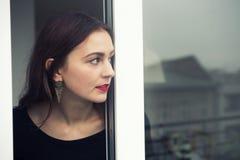 Портрет молодой женщины смотря из окна Стоковое Изображение