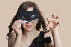 Портрет молодой женщины смотря через маску глаза имитируя как кот над покрашенной предпосылкой Стоковая Фотография RF