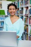 Портрет молодой женщины с компьтер-книжкой в библиотеке Стоковое Изображение