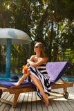 Портрет молодой женщины с стеклом коктеиля около бассейна на шезлонге с пальмами позади красивейшие детеныши женщины каникулы бас Стоковые Фотографии RF