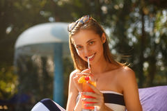 Портрет молодой женщины с стеклом коктеиля около бассейна на шезлонге с пальмами позади красивейшие детеныши женщины каникулы бас Стоковое фото RF