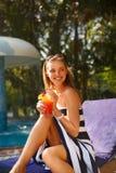 Портрет молодой женщины с стеклом коктеиля около бассейна на шезлонге с пальмами позади красивейшие детеныши женщины каникулы бас Стоковые Фото