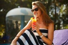 Портрет молодой женщины с стеклом коктеиля около бассейна на шезлонге с пальмами позади красивейшие детеныши женщины каникулы бас Стоковая Фотография RF