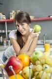 Портрет молодой женщины с яблоком в кухне стоковые изображения